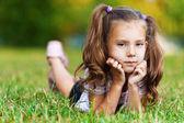 On grass is pretty sad little girl