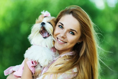 Photo for Portrait of pretty, young, smiling woman holding small fluffy dog, against background of summer green park - Royalty Free Image