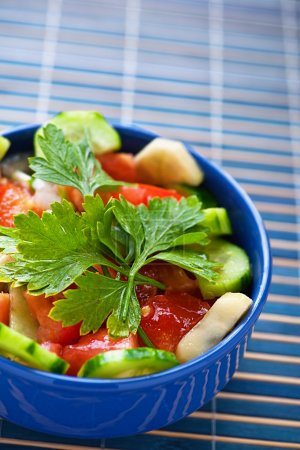 Photo for Summer vegetable salad with tomatoes and cucumbers garnished with parsley sprig in blue deep bowl, next is fork, all blue napkin - Royalty Free Image