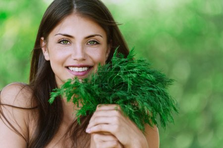 Photo for Portrait beautiful young woman smiling holding bunch green dill background summer green park - Royalty Free Image