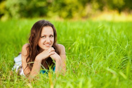 Photo for Beautiful young smiling woman lying green grass - Royalty Free Image