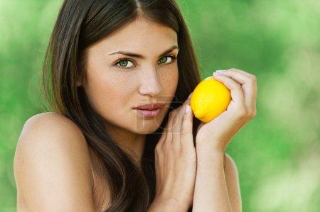 Beautiful young woman holding lemon