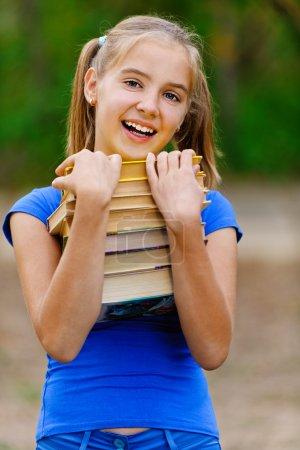 Teenager girl holding stack of seven books