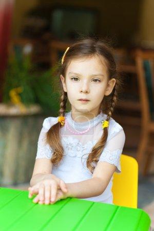 Photo pour Petite fille assise à la table des enfants verts et pensant . - image libre de droit
