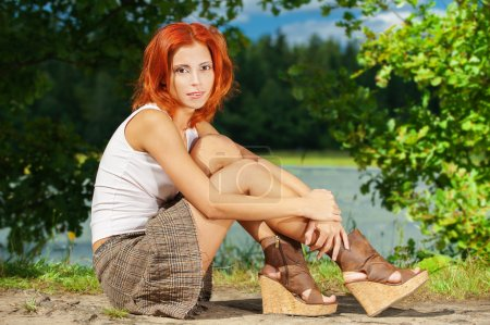 Photo for Carroty beautiful woman sitting on shore of lake, on green park summer. - Royalty Free Image