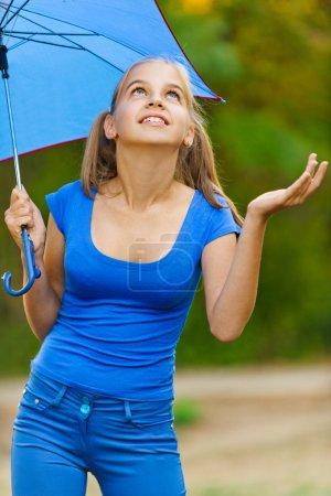 Teenager girl holding umbrellas