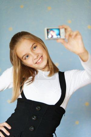 Photo pour Belle aux yeux bleus fille-adolescent photographié avec l'appareil photo lui-même, sur fond bleu. - image libre de droit