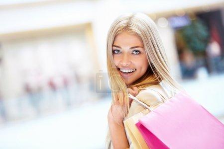 Photo pour Souriante fille avec des sacs à provisions dans la boutique - image libre de droit