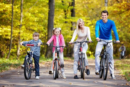 Photo for Family on bikes in the park in autumn - Royalty Free Image