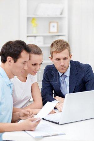 Photo pour Le consultant et le jeune couple pour un ordinateur portable - image libre de droit