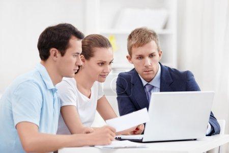 Photo pour Consultant chez un couple à la recherche à l'ordinateur portable - image libre de droit