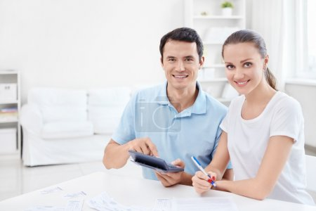 Photo for Man and woman with a calculator at home - Royalty Free Image