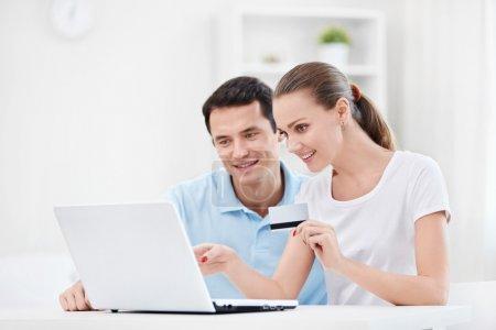 Photo pour Un couple avec une carte de crédit et un ordinateur portable à la maison - image libre de droit