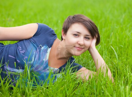 Young Woman relaxing on the green grass