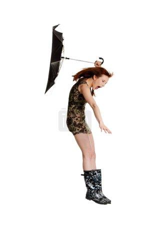 Foto de Joven mujer con paraguas soplada por el viento. aislado en blanco backgroiund - Imagen libre de derechos