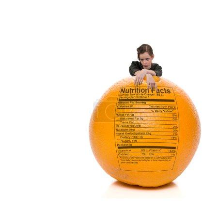 Photo pour Une belle jeune femme adolescente debout derrière une orange avec un étiquetage nutritionnel - image libre de droit