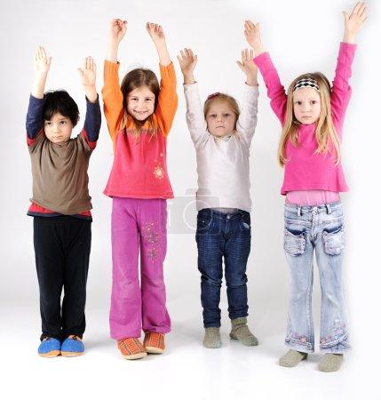Photo pour Groupe de quatre enfants les bras levés - image libre de droit