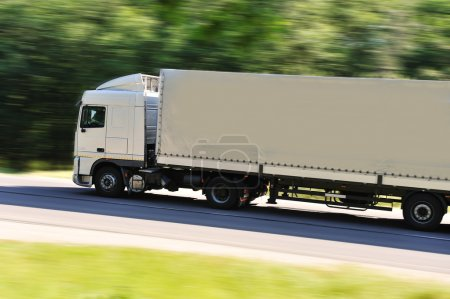 Fast moving truck with white container on highway