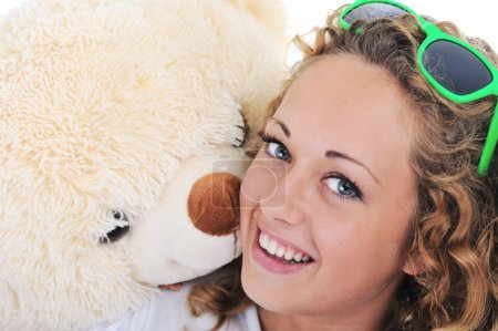 Teenage blond girl holding a teddy bear