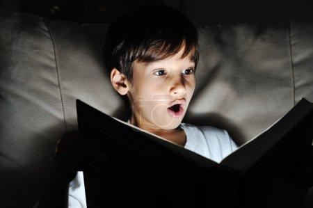 Shocked kid reading book, light in darkness