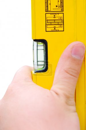 Hand holding yellow level tool