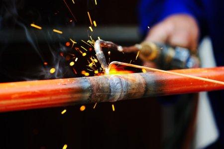 Photo pour Soudeur utilisant la torche sur l'objet métallique - image libre de droit