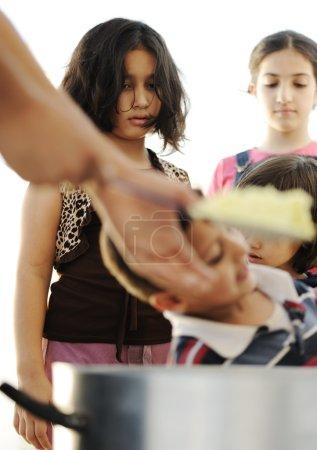 Photo pour Enfants qui ont faim dans le camp de réfugiés, distribution de nourriture humanitaire - image libre de droit