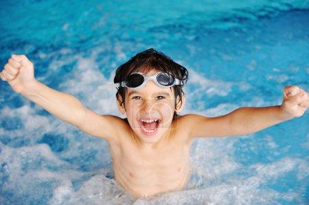 Photo pour Super heureux garçon à l'intérieur de la piscine - image libre de droit