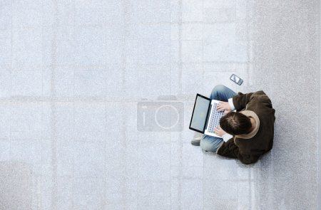 Young man sitting on the floor and surfing on laptop with large copy-space