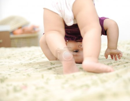 Baby boy playing upside down in bedroom