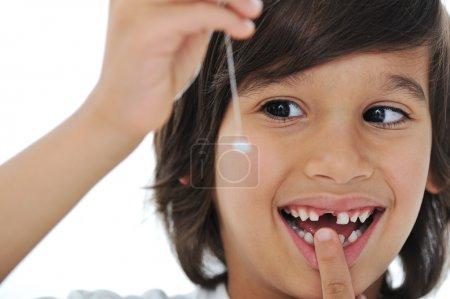 Photo pour Dents lait perdu, mignon garçon avec des cheveux longs, tenant sa dent sur fil - image libre de droit