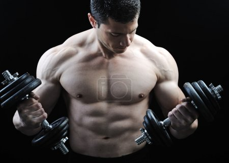 Photo for The Perfect male body - Awesome bodybuilder posing with dumbbells - Royalty Free Image