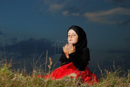 Photo pour Petite fille musulmane sur la prairie, avant le coucher du soleil - image libre de droit
