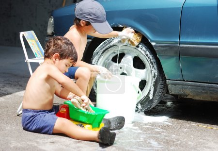 A little cute kid is cleaning car, outdoor
