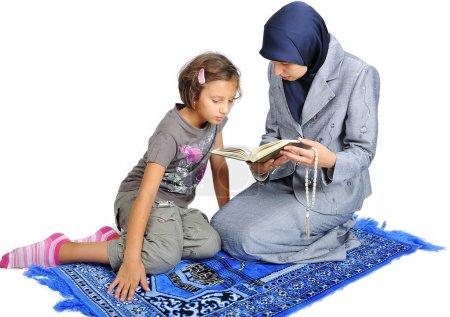 Young nice muslim female teaching her daughter