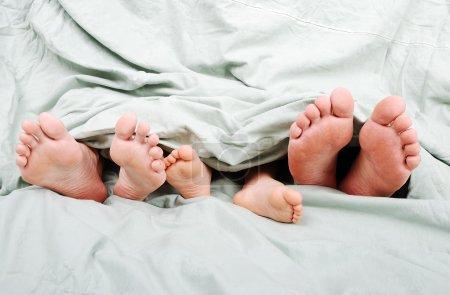 Happy familiy in bed under sheet