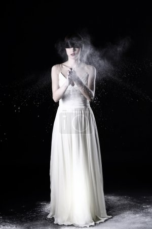 Beautiful girl in white dress and flying dust