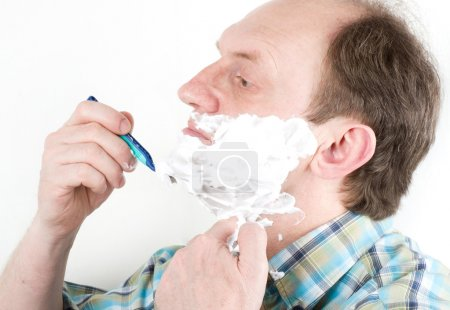 Portrait of mature handsome man shaving his beard