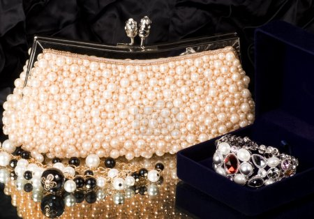 Sexy fashionable handbag with pearl jewelry on black background