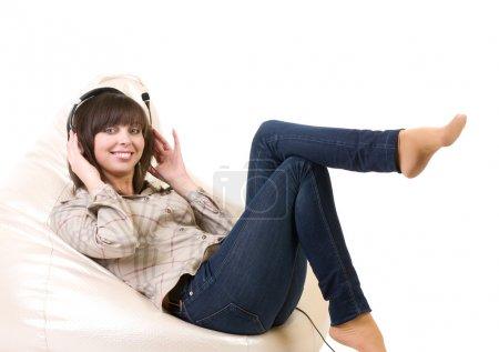 Photo pour Belle jeune femme avec casque est d'écouter la musique sur fond blanc . - image libre de droit