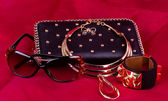 Fashionable handbag and golden jewelry, glasses on red background.