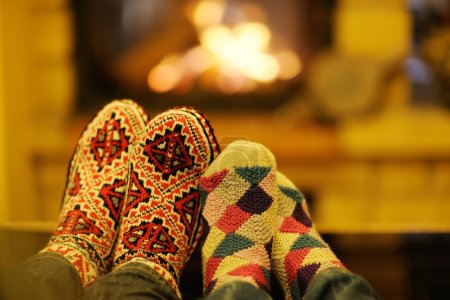 Young romantic couple sitting on sofa in front of fireplace at home