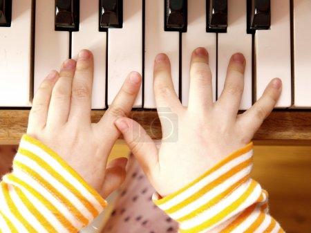 Photo pour Gros plan des mains de l'enfant, jouer du piano - image libre de droit