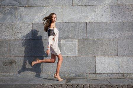 Photo pour Belle jeune femme s'exécute contre un mur de Pierre - image libre de droit