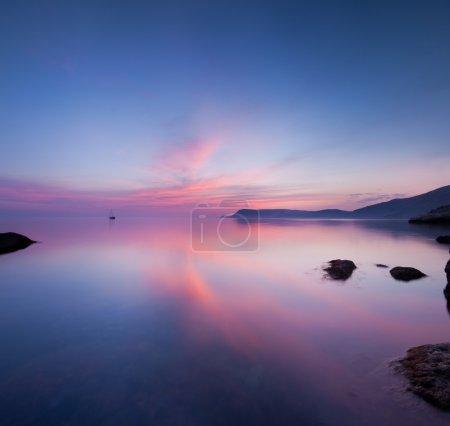 Photo pour Mer lisse après le coucher du soleil avec le bateau à l'horizon - image libre de droit