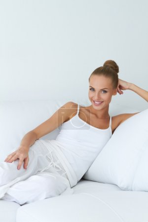 Relaxed beautiful woman sitting on couch