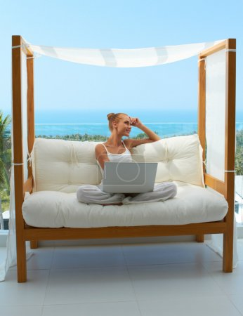 Woman with laptop on canopied seat