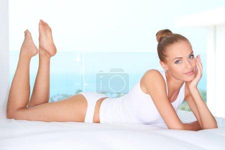 Beautiful woman lying on white bed