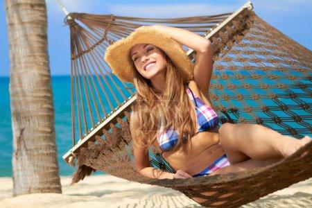 Beautiful tourist relaxing in a hammock