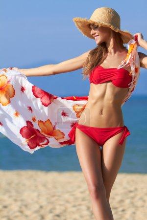 Beautiful blonde in a red bikini at the ocean